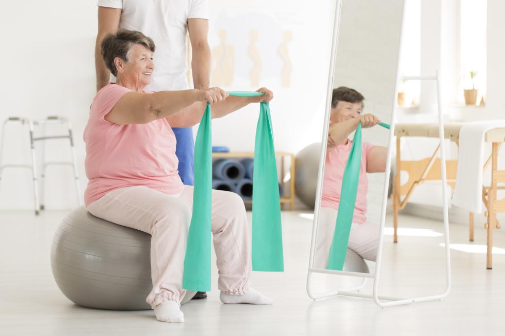 ältere Frau trainiert mit Gummiband