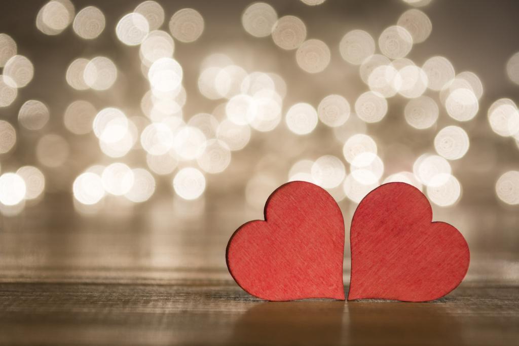 Zwei Herzen aus Holz vor Kerzenlicht