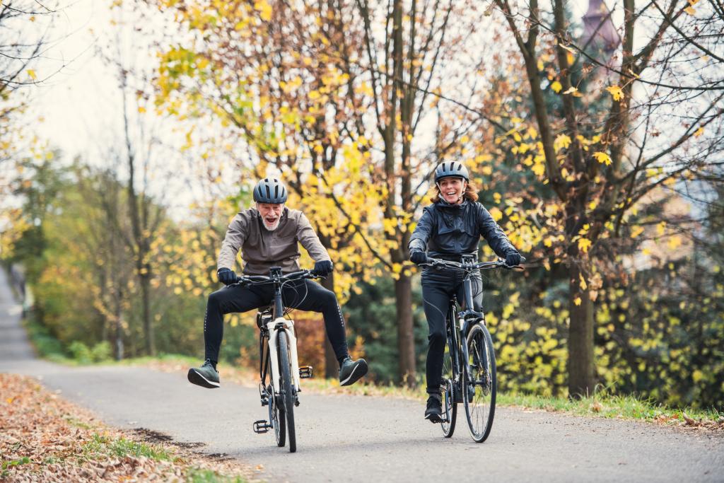 Zwei Menschen fröhlich auf E-Bikes