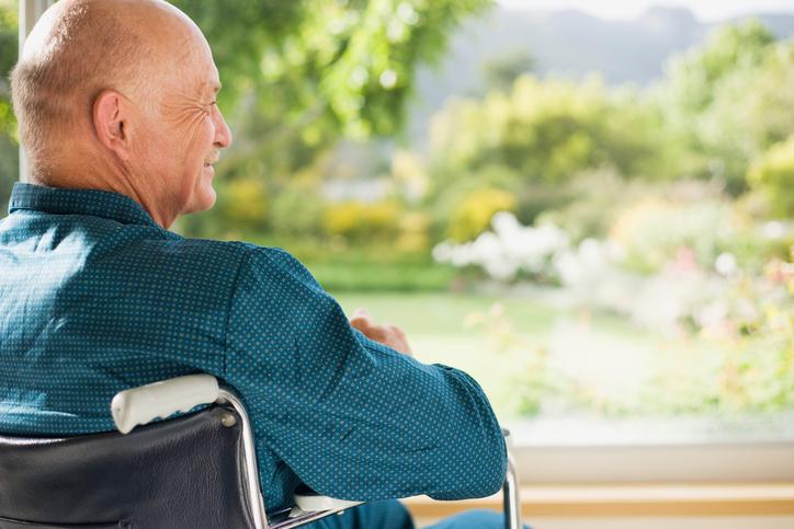 Mann im Rollstuhl schaut aus dem Fenster