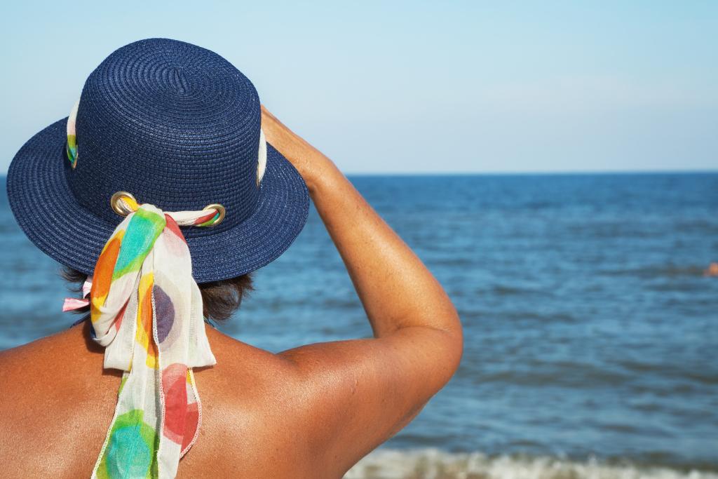 Frau mit Sonnenhut von hinten