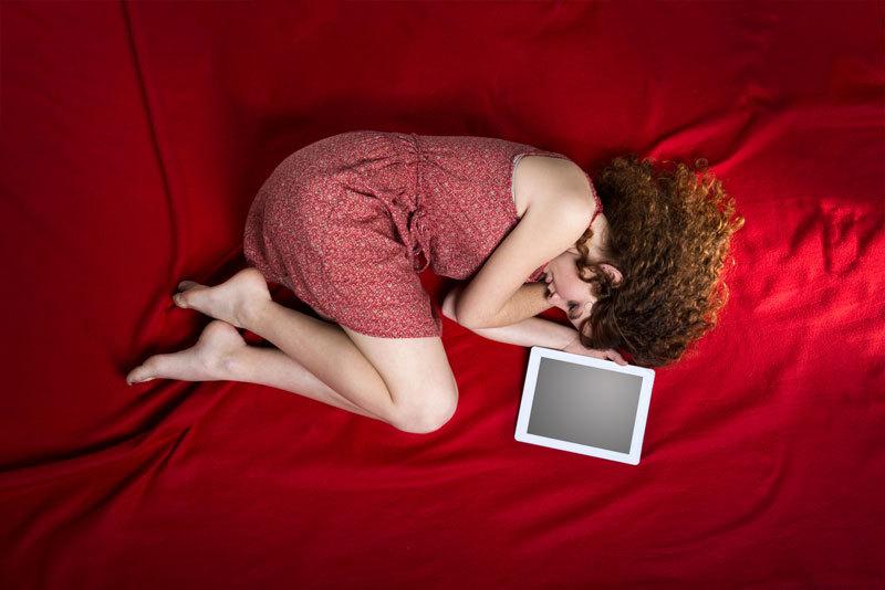 Frau liegt traurig auf einem Bett, neben ihr ein Tablet