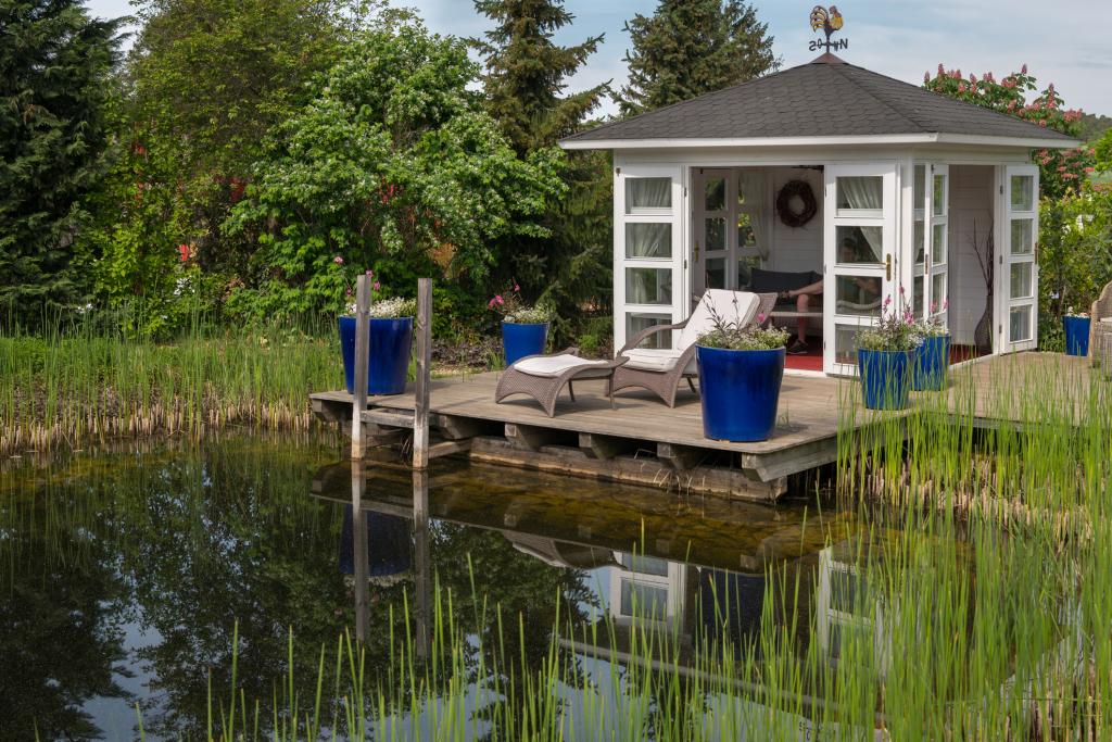 Schwimmteich mit Gartenhäuschen und kleinem Steg