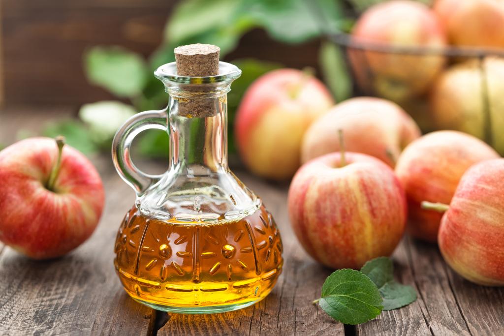 Äpfel und eine kleine Flasche mit Apfelessig