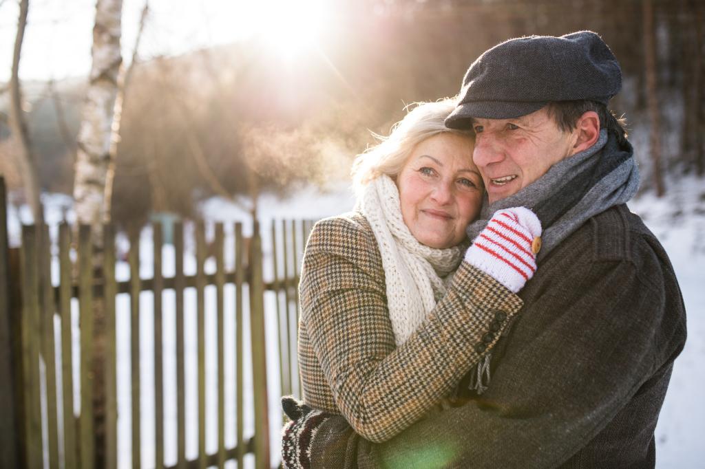 Älteres Paar umarmt sich in Winersonne