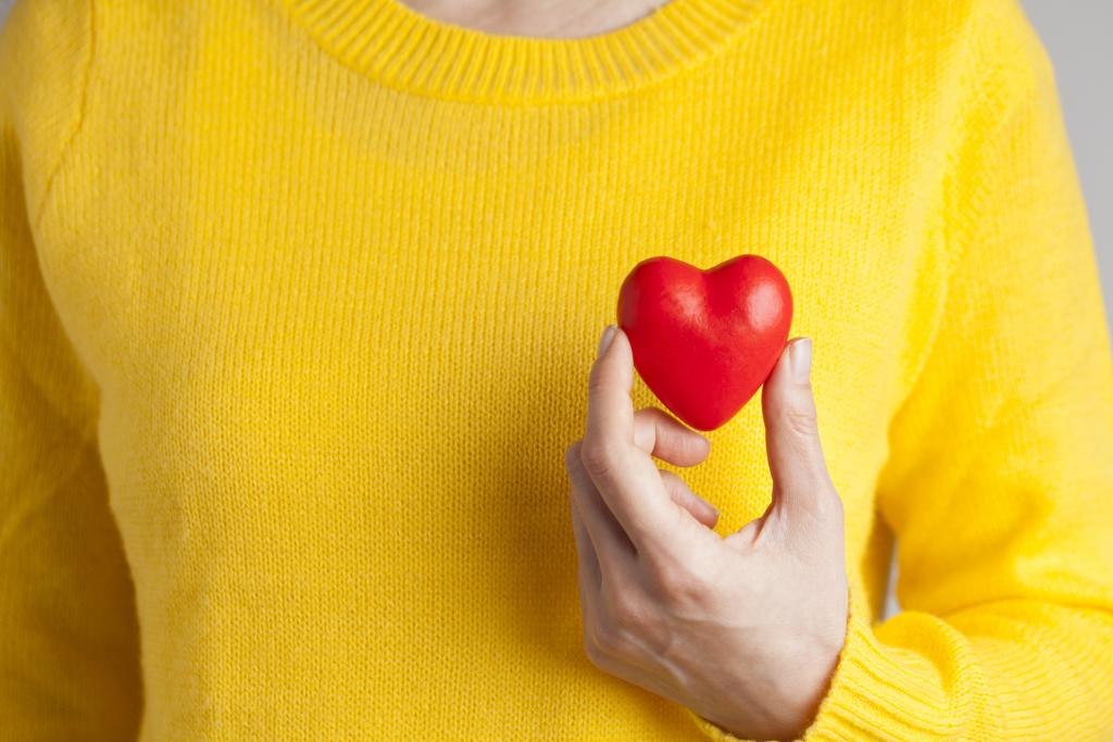 Hand, die ein kleines rotes Herz vor einem gelben Pulli hält