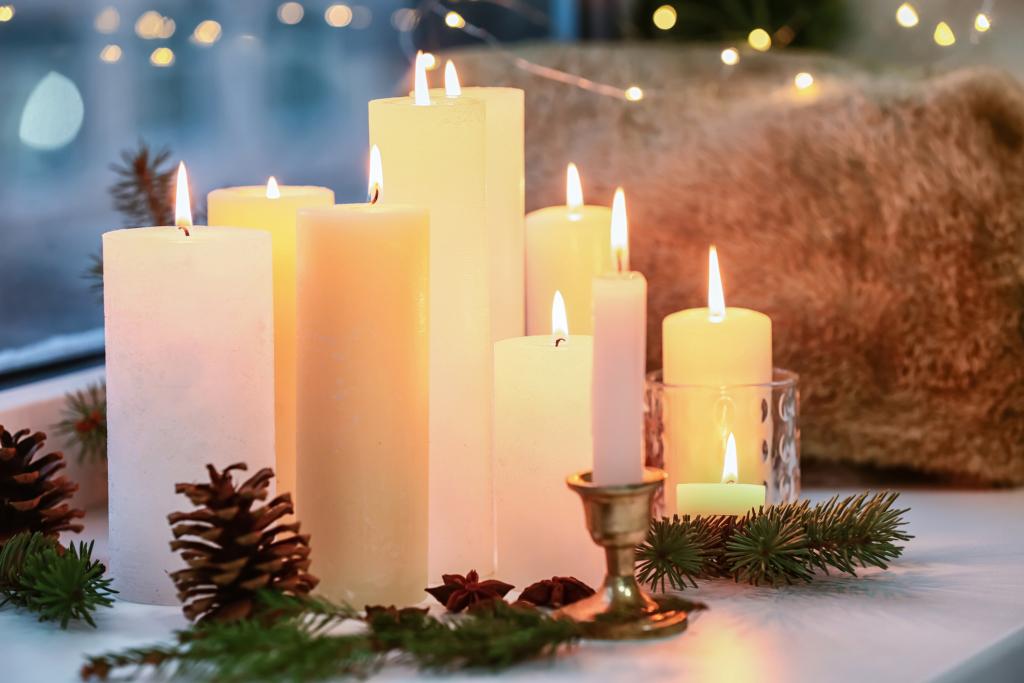 Kerzen auf Fensterbank mit winterlicher Dekoration