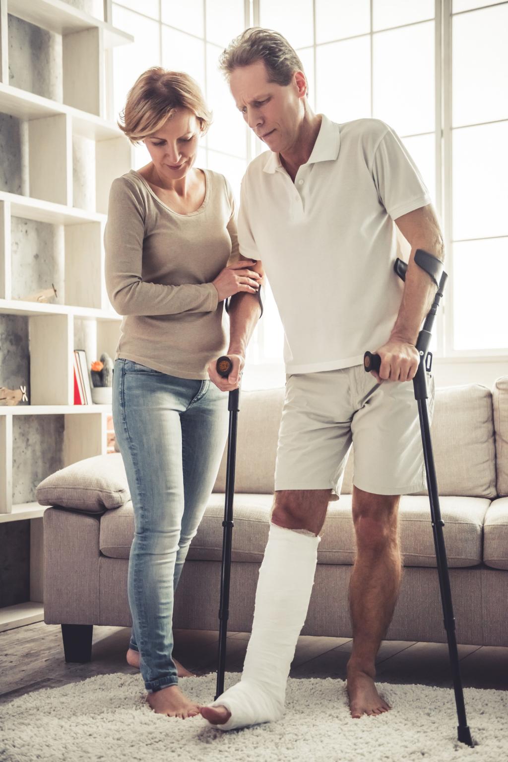 Frau unterstützt Mann mit gebrochenem Bein