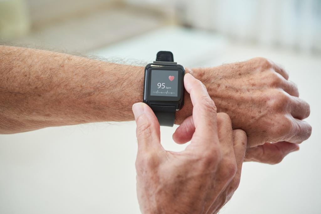 Smartwach am Handgelenk eines Seniors mit Puls in der Anzeige