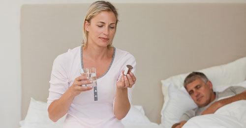 Frau blickt auf Tablettenroehrchen