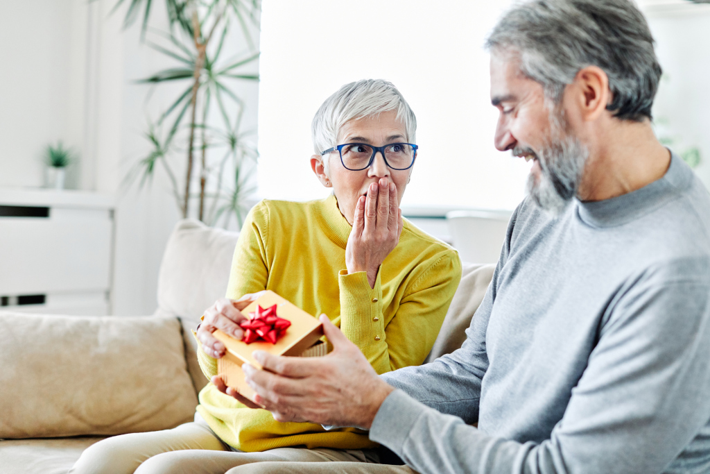Seniorpaar, er überrascht sie mit Geschenk