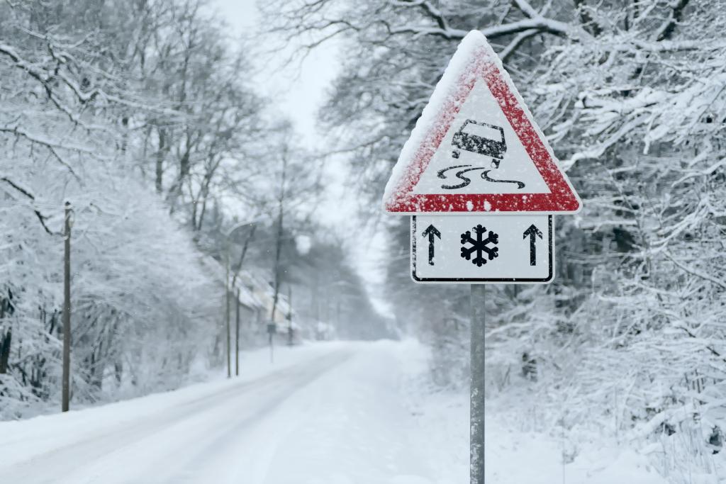 Verschneite Straße mit Verkehrsschild