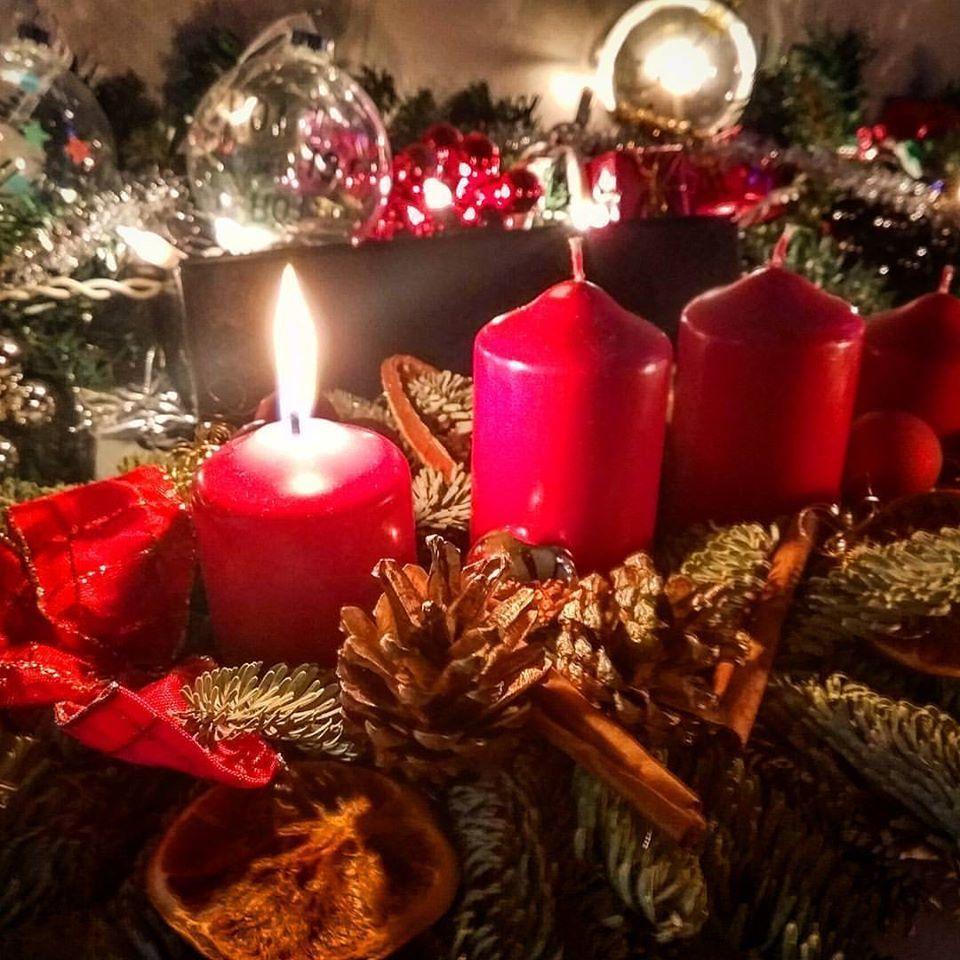 eine entzündete Kerze auf einem Adventskranz