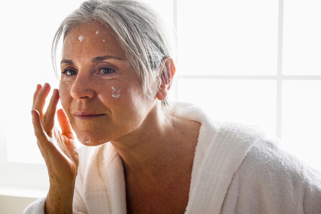 Frau beim Gesichtseincremen