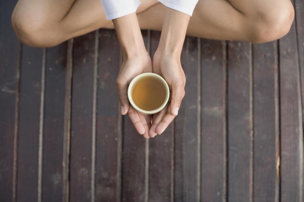 Frau mit Teetasse in zwei Händen