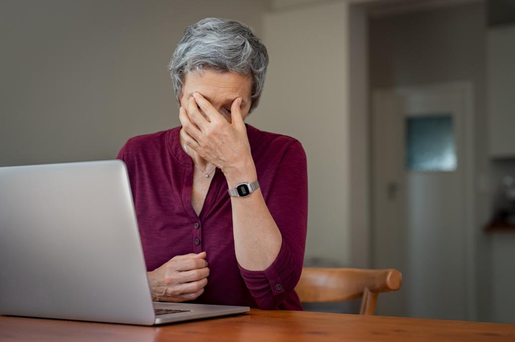 Frau stützt vor dem PC sitzend ihren Kopf erschöpft in die Hand