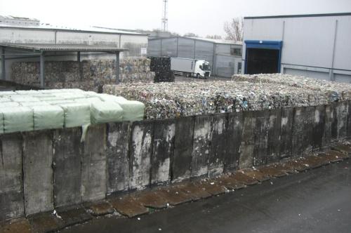Teile der Berliner Mauer werden als Stützen für die Ballen verwendet.