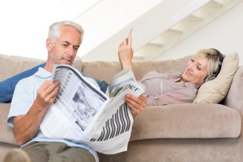 Paar liest auf Tablet und in einer Zeitung