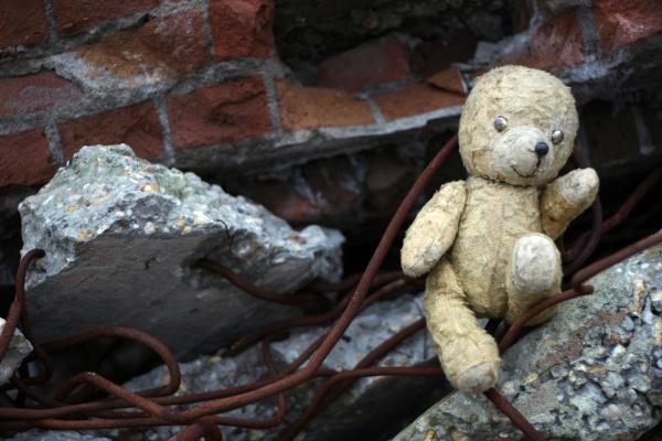 Verbrannter Teddybär vor Ruine