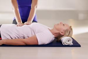 Reiki-Behandlung einer auf dem Boden liegenden Frau