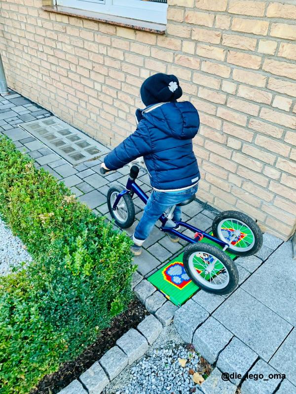 Kleiner Junge mit Laufrad auf Legorampe