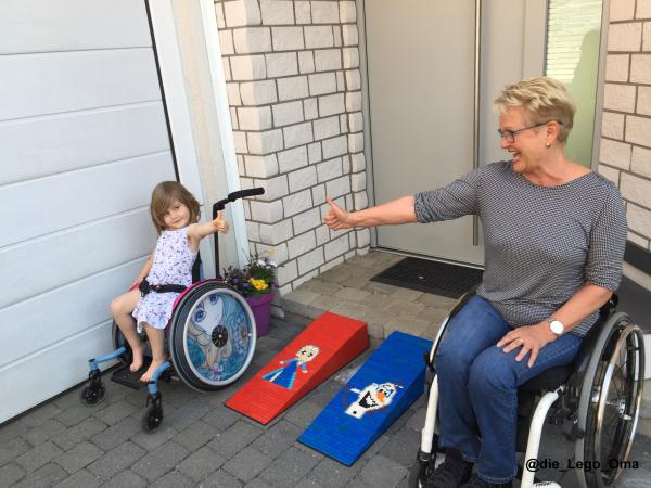 Lego-Oma Rita Ebel und ein kleines Mädchen vor den Rollstuhlrampen