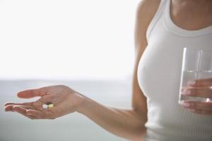 Frau mit Tabletten auf der Hand