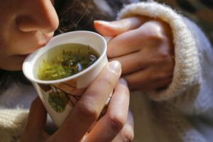 Frau trinkt Tee mit frischen Kräutern