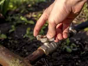 Nahaufnahme Hand an Ventil Wasserhahn im Garten