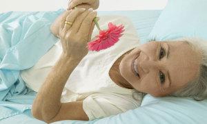 Frau im Bett mit Blume