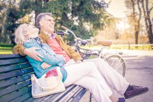 lachendes Paar auf einer Parkbank