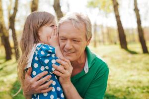 kleines Mädchen flüstern älterem Mann etwas ins Ohr