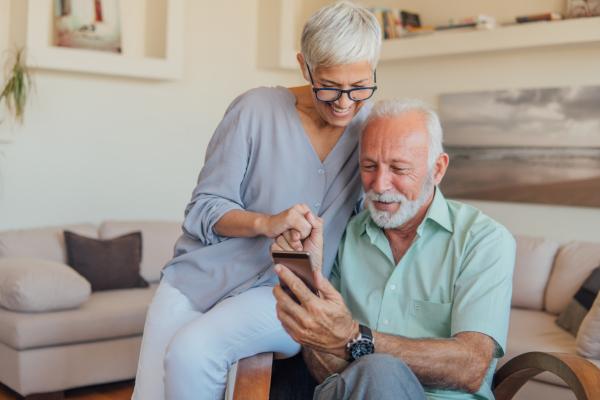 Paar, das sich lachend über ein Smartphone beugt