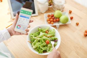Smartphone und Salat im Hintergrund