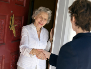 ältere Frau und jüngere Person an der Haustür
