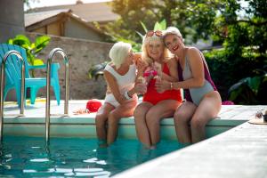 drei ältere Frauen mit Spaß am Pool