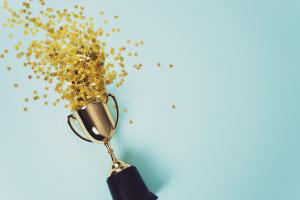 Goldpokal, aus dem goldenes Konfetti kommt