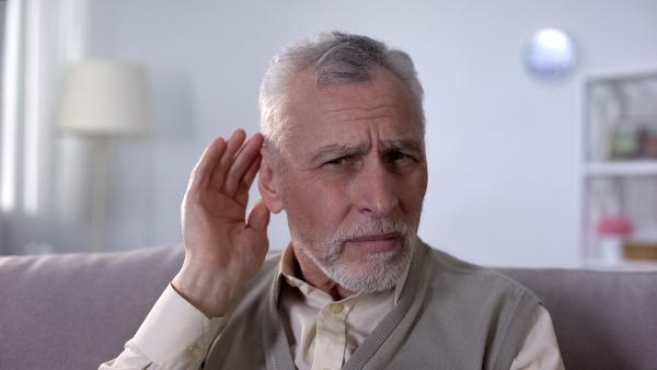 Mann hört schlecht und hält Hand hinters Ohr
