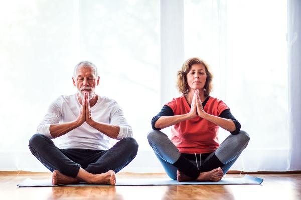 Seniorenpaar macht Yoga