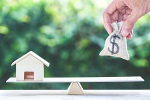 Waage mit Haus und Geld
