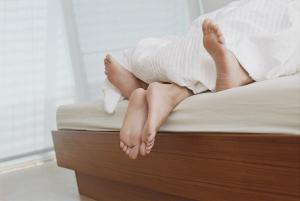 Füße schauen unter der Bettdecke raus