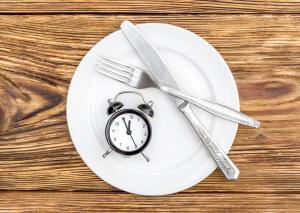 leerer Teller mit Besteck und einem Wecker