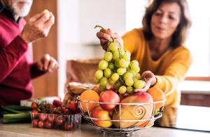 älteres Paar in der Küche, Gemüse und Obstschale