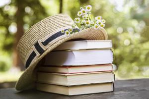 Bücherstapel mit Strohhut