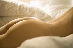 Po und Rücken einer nackten Frau auf dem Bett