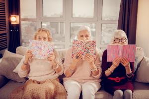 drei Frauen mit einem Buch vor dem Gesicht