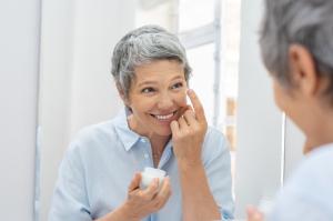 Ältere Dame, die sich Creme vor einem Spiegel aufträgt.