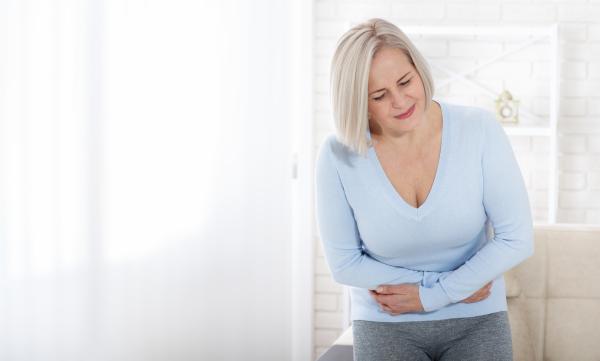 Frau leidet unter Bauchschmerzen und verschränkt die Arme vor dem Bauch