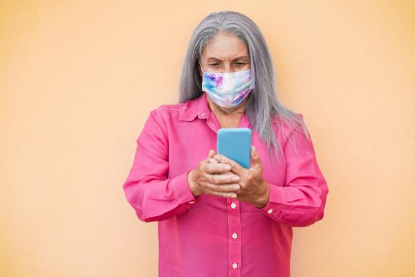 Ältere Damen mit Gesichtsmaske am Smartphone