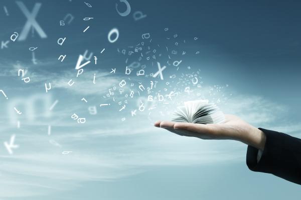 geöffnetes Buch auf einer Hand, in das Buchstaben fliegen